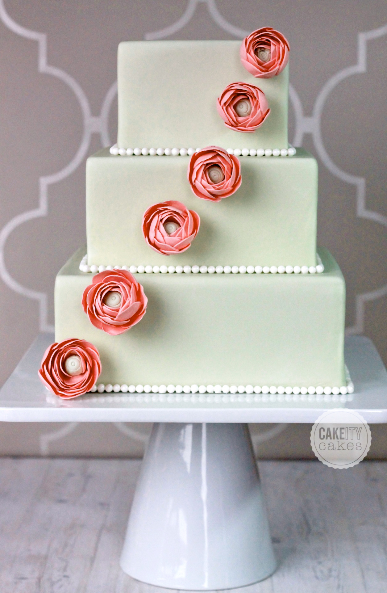 Pastel green square wedding cake with red sugar flowers