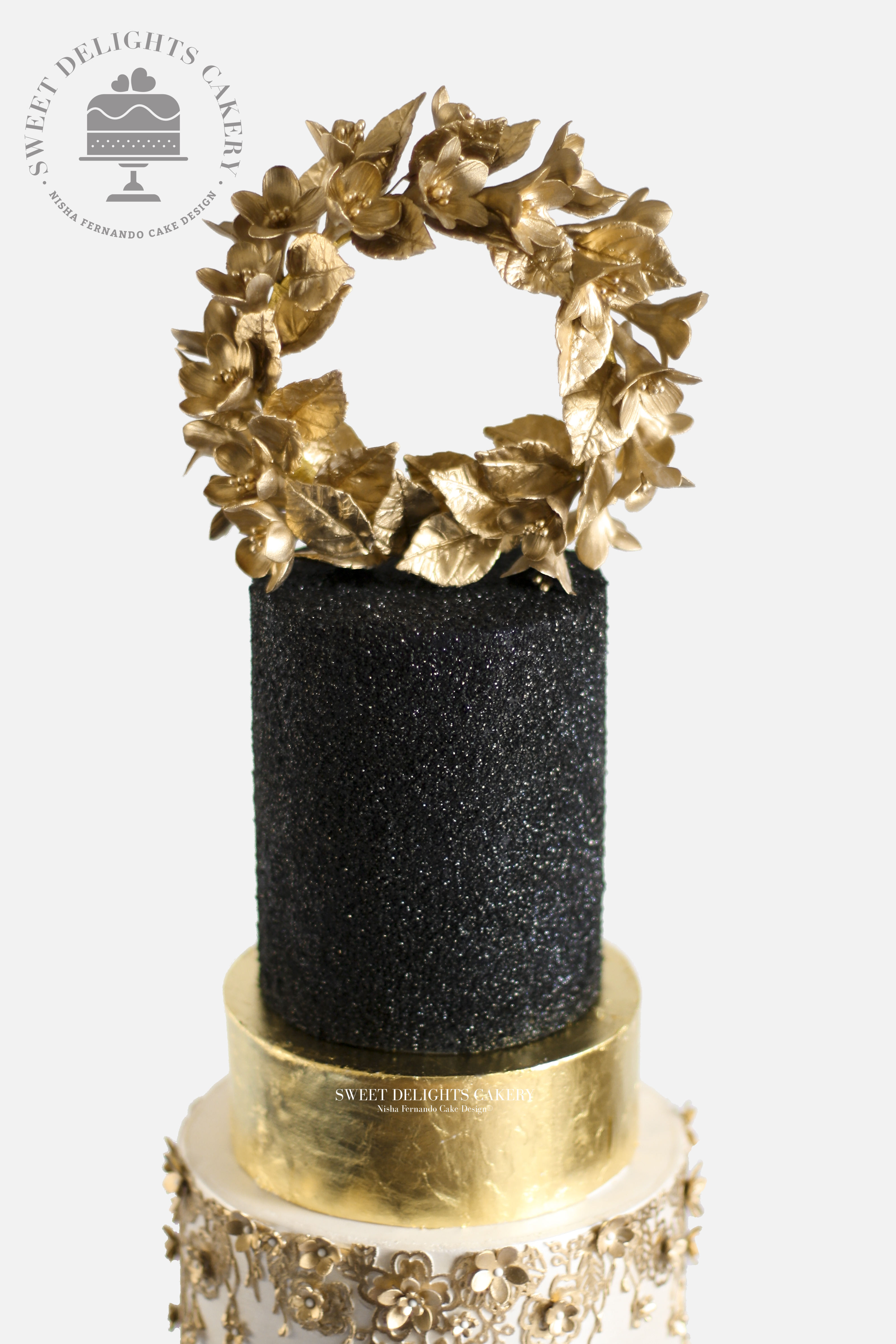 Black glam wedding cake with gold wreath