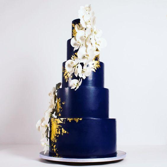 Navy blue wedding cake with gold and white sugar flowers