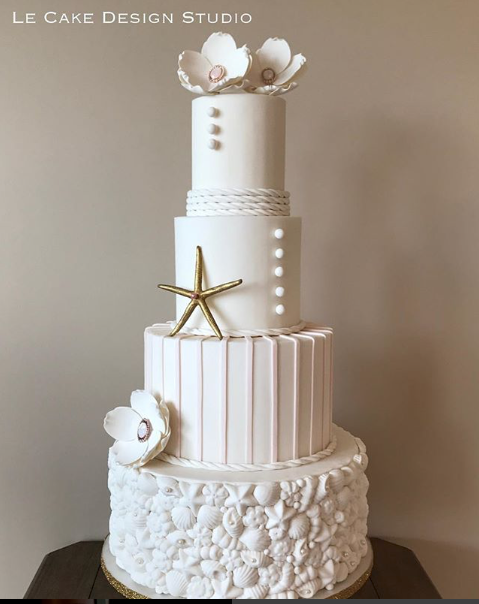 All white beach themed wedding cake with starfish and seashell detailing