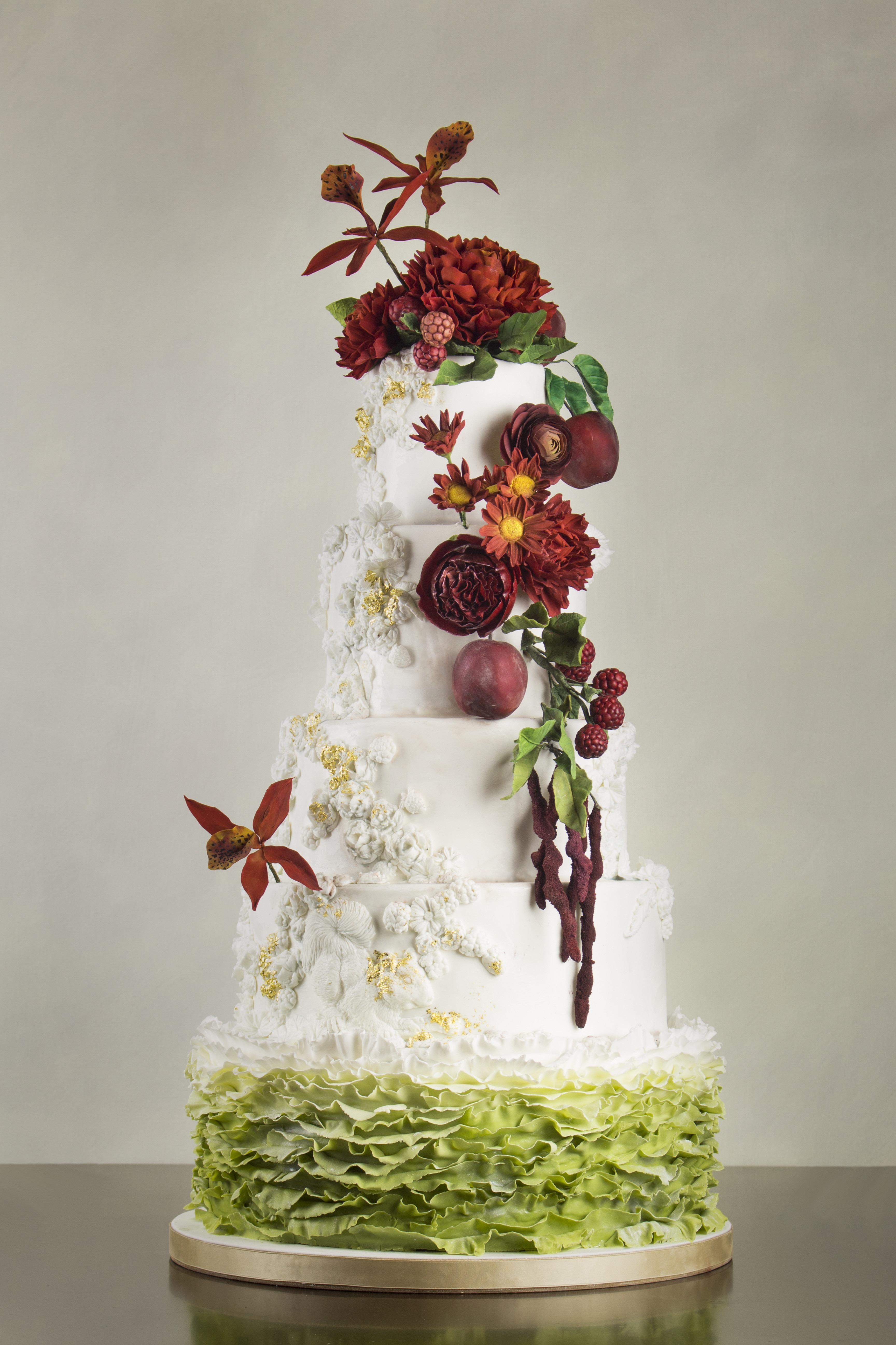 White wedding bas relief wedding cake with green ombre ruffles and dark red sugar flowers