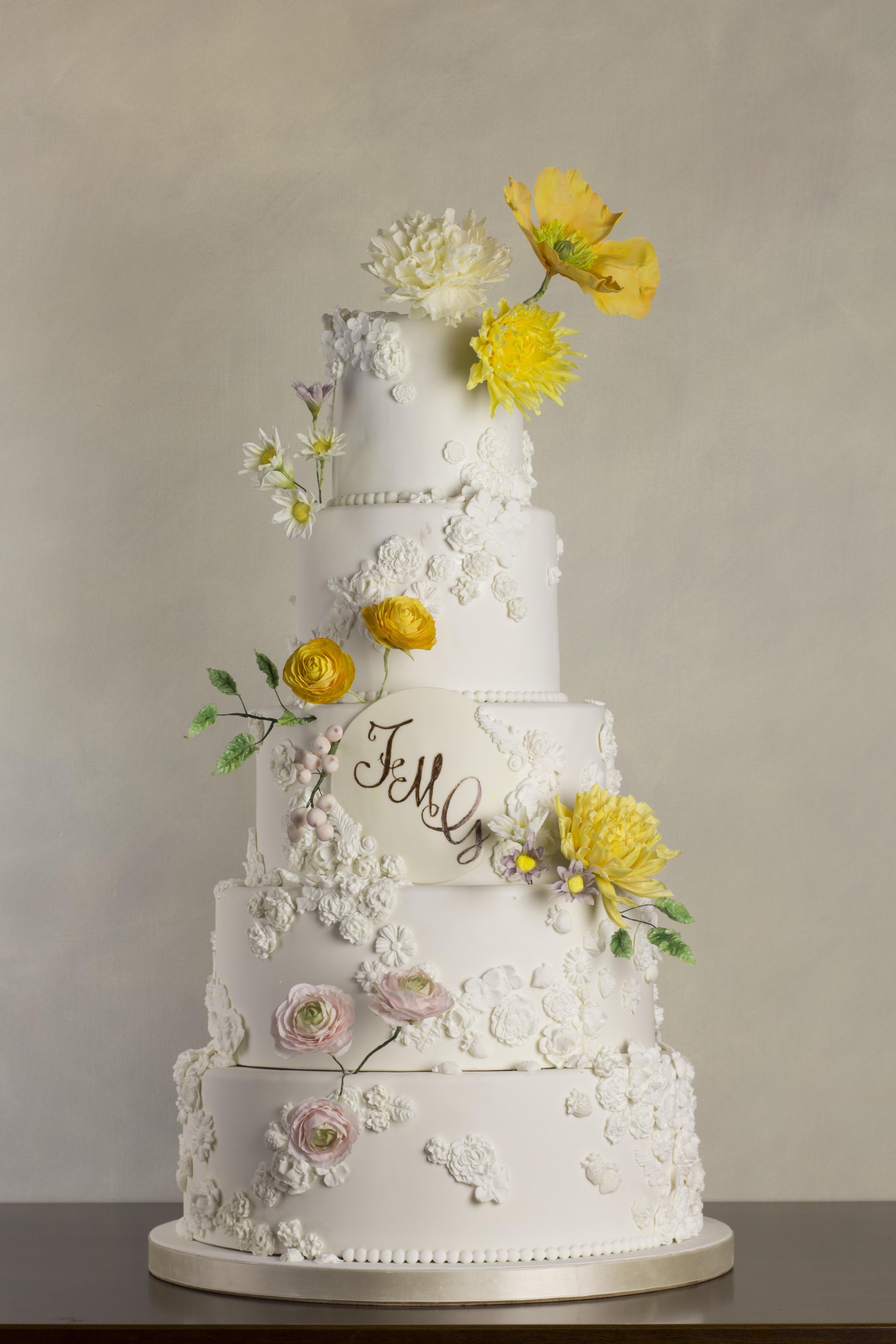 White wedding cake with yellow sugar flowers