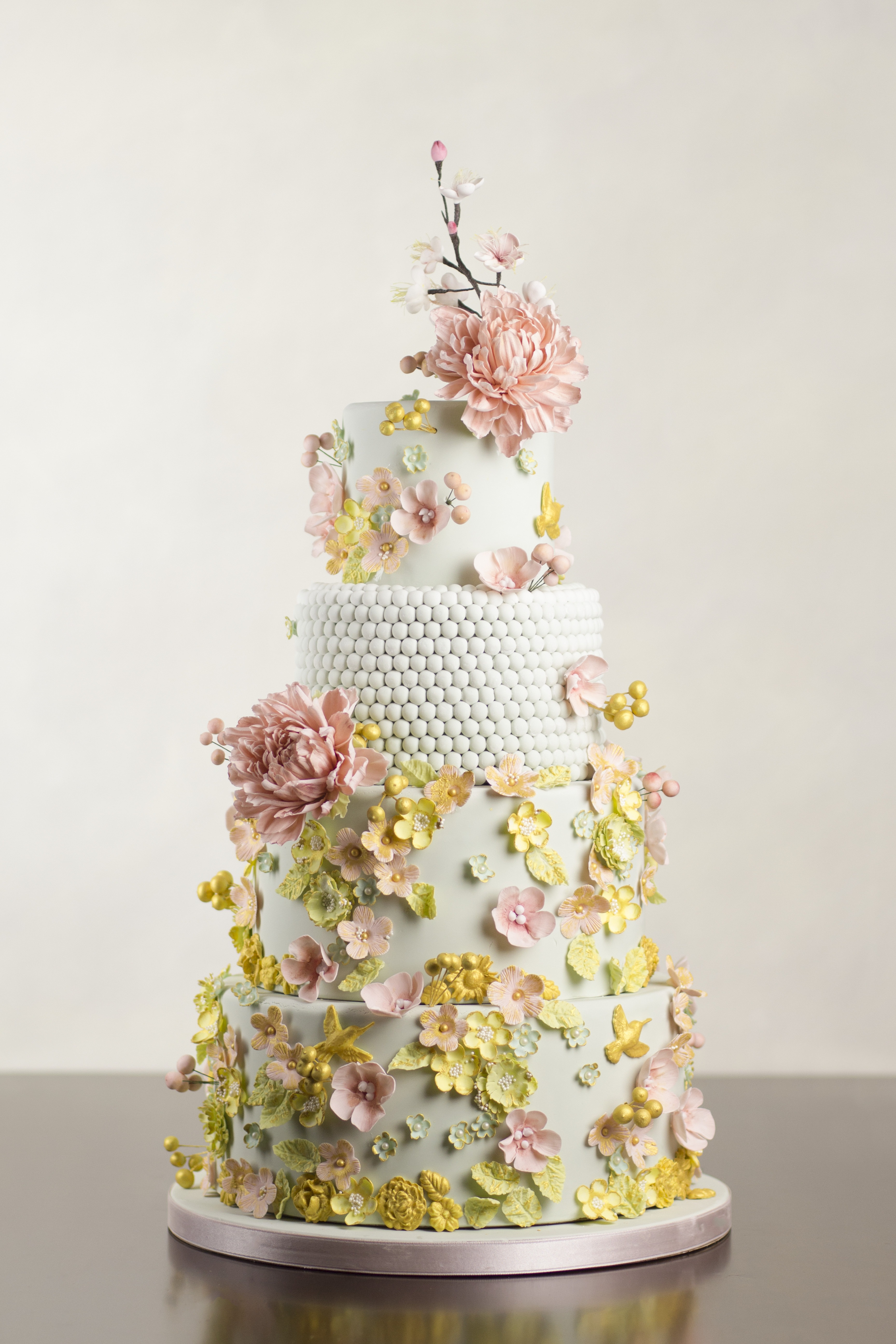 Pastel green wedding cake with sugar pearls and all over sugar flowers