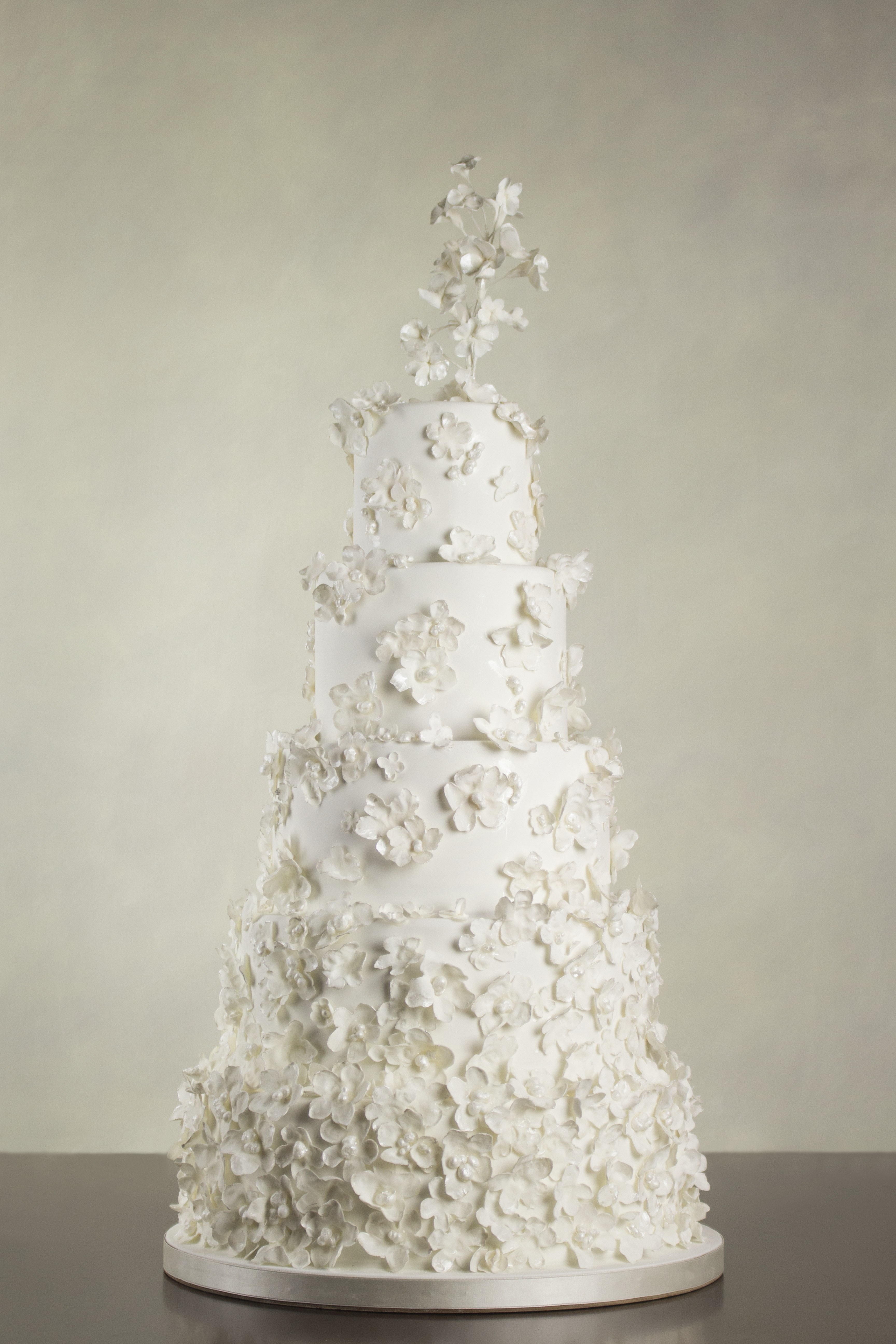 All white wedding cake covered in white flowers