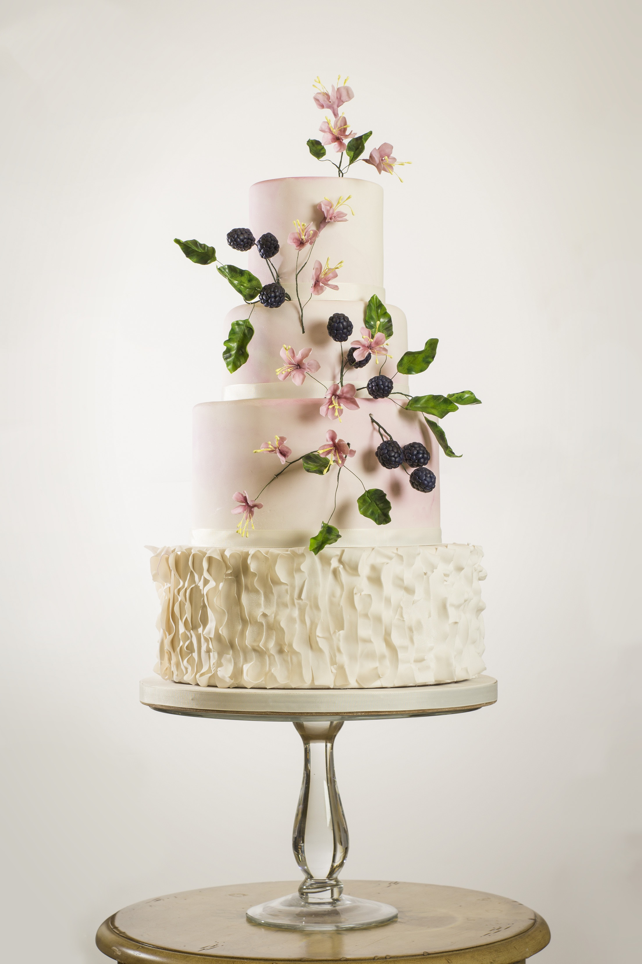 Light pink wedding cake with ruffles and sugar berries