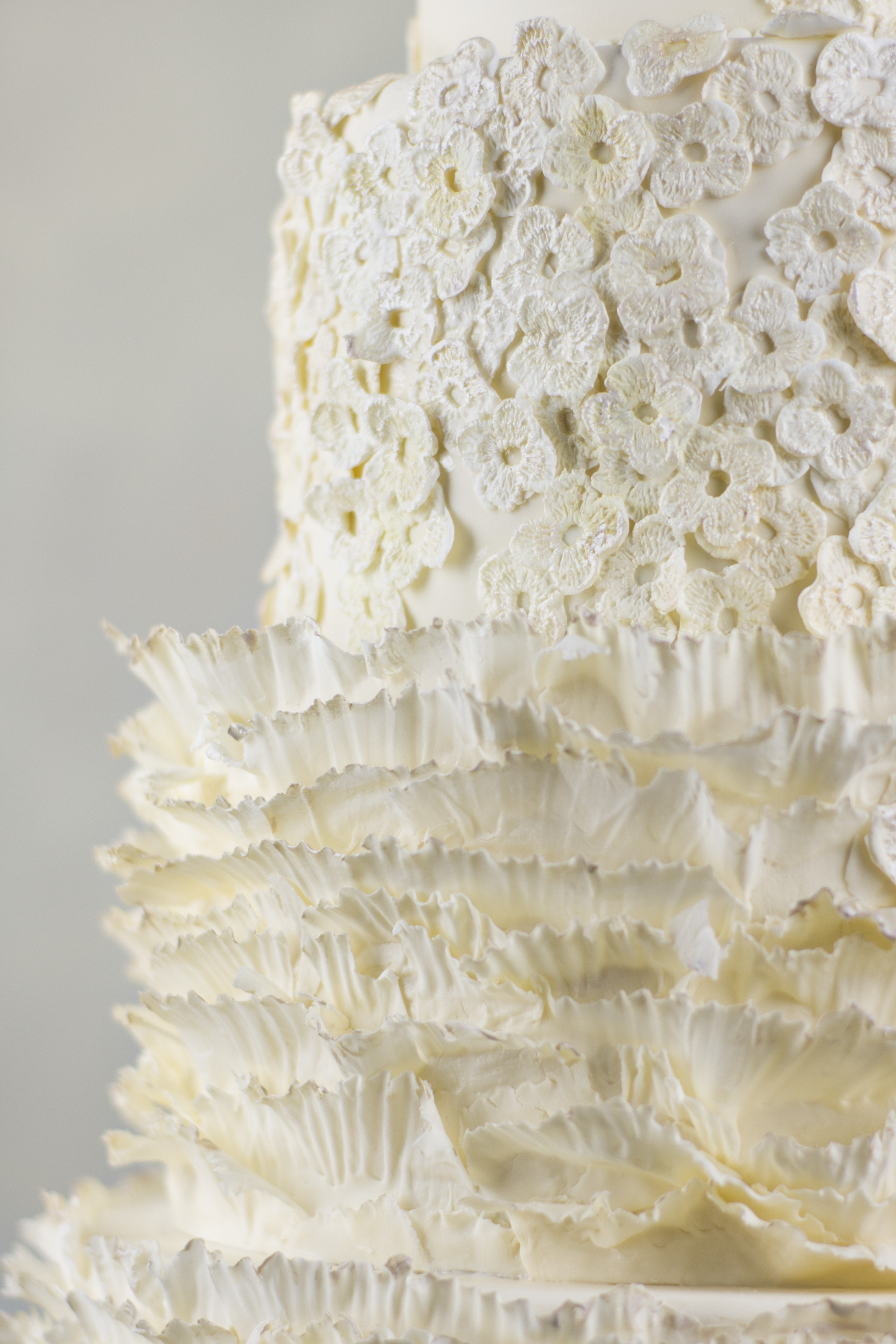 All white bas relief and textured fondant ruffle wedding cake