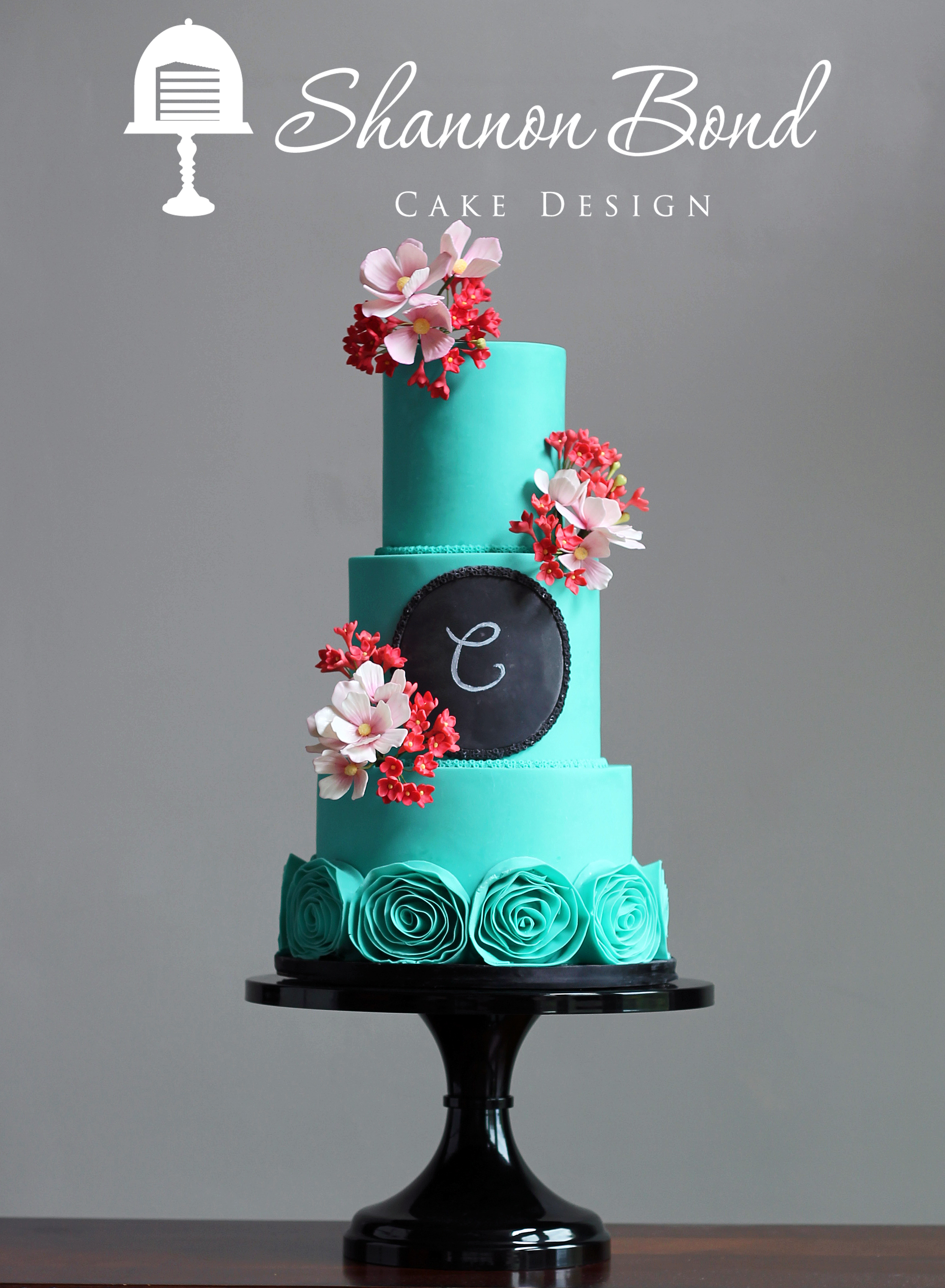 Turquoise wedding cake with rosettes and red sugar flowers