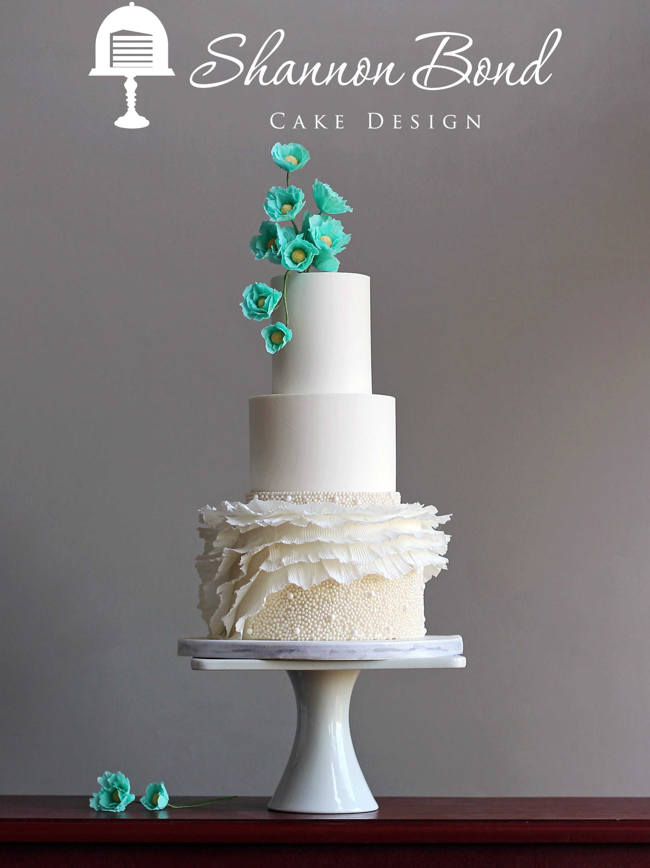 White wedding cake with turquoise sugar flowers