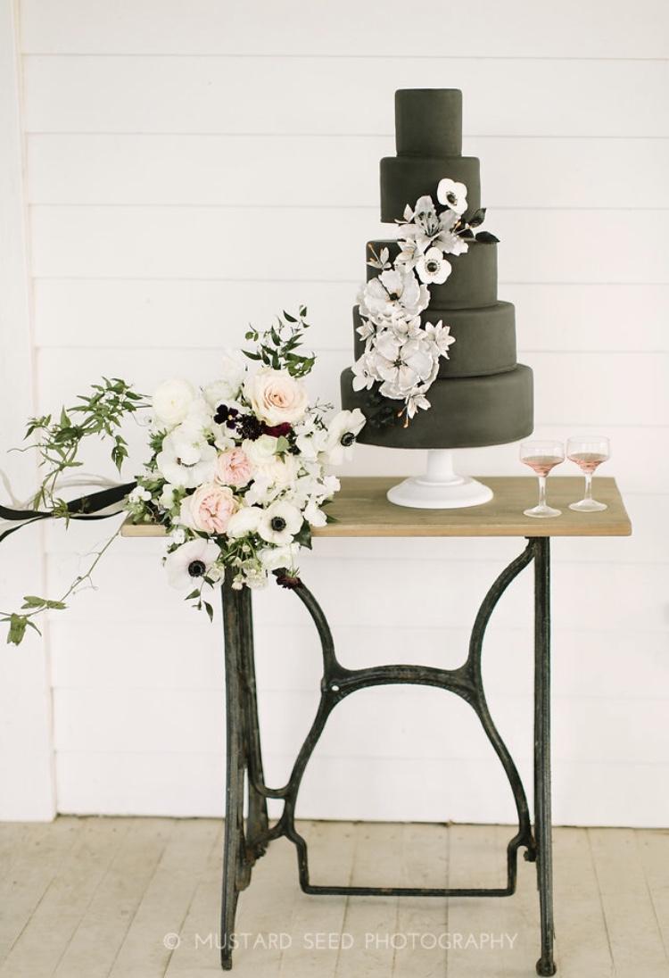 Matte black wedding cake with white sugar flowers