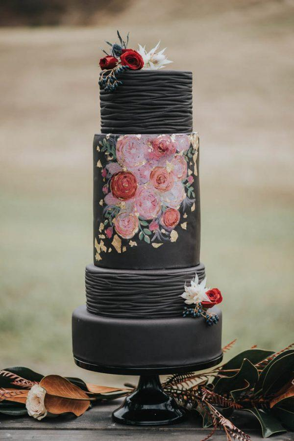 Black wedding cake with hand painted roses on front