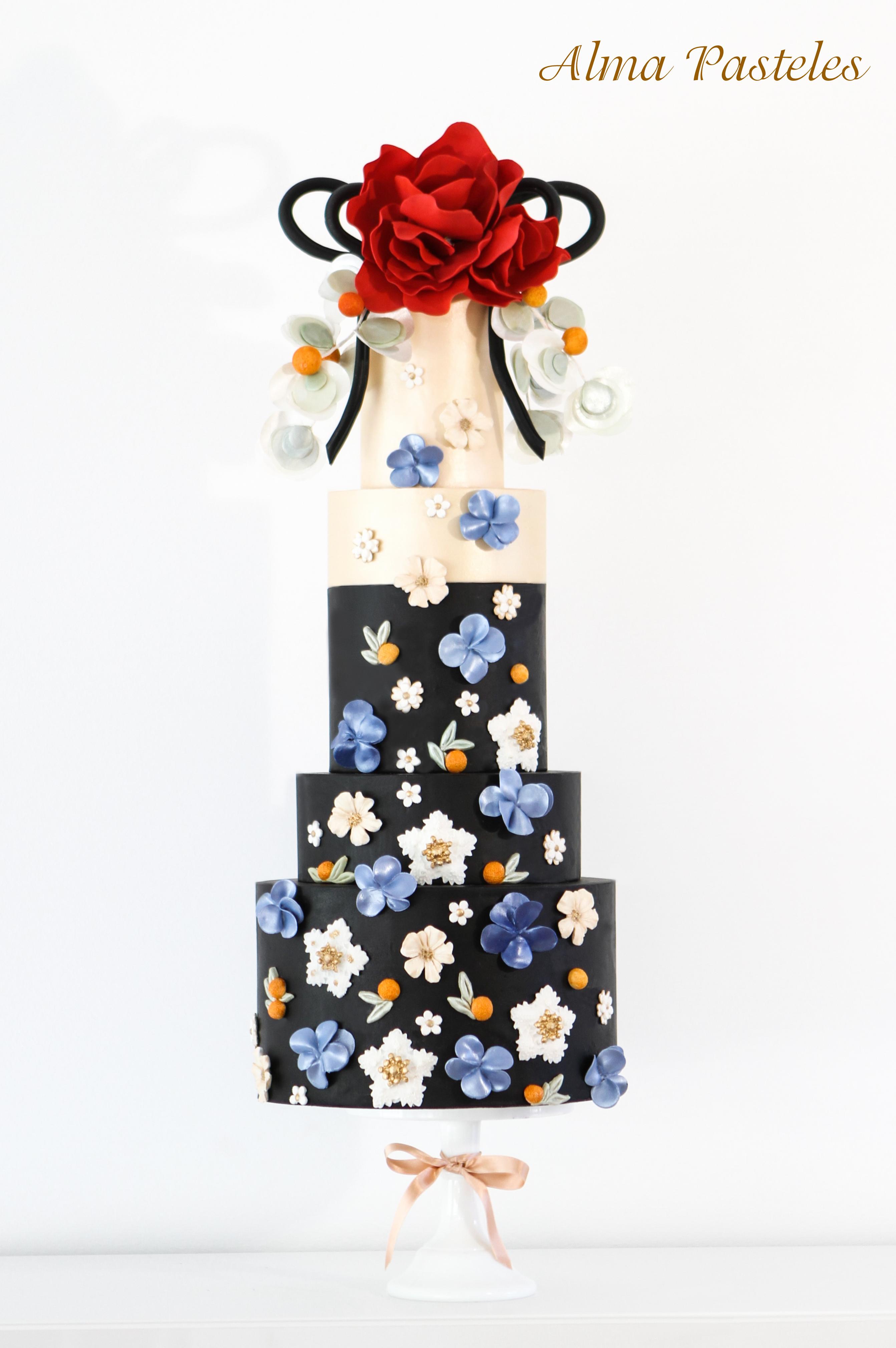 Ivory and black wedding cake with blue sugar flower appliqué
