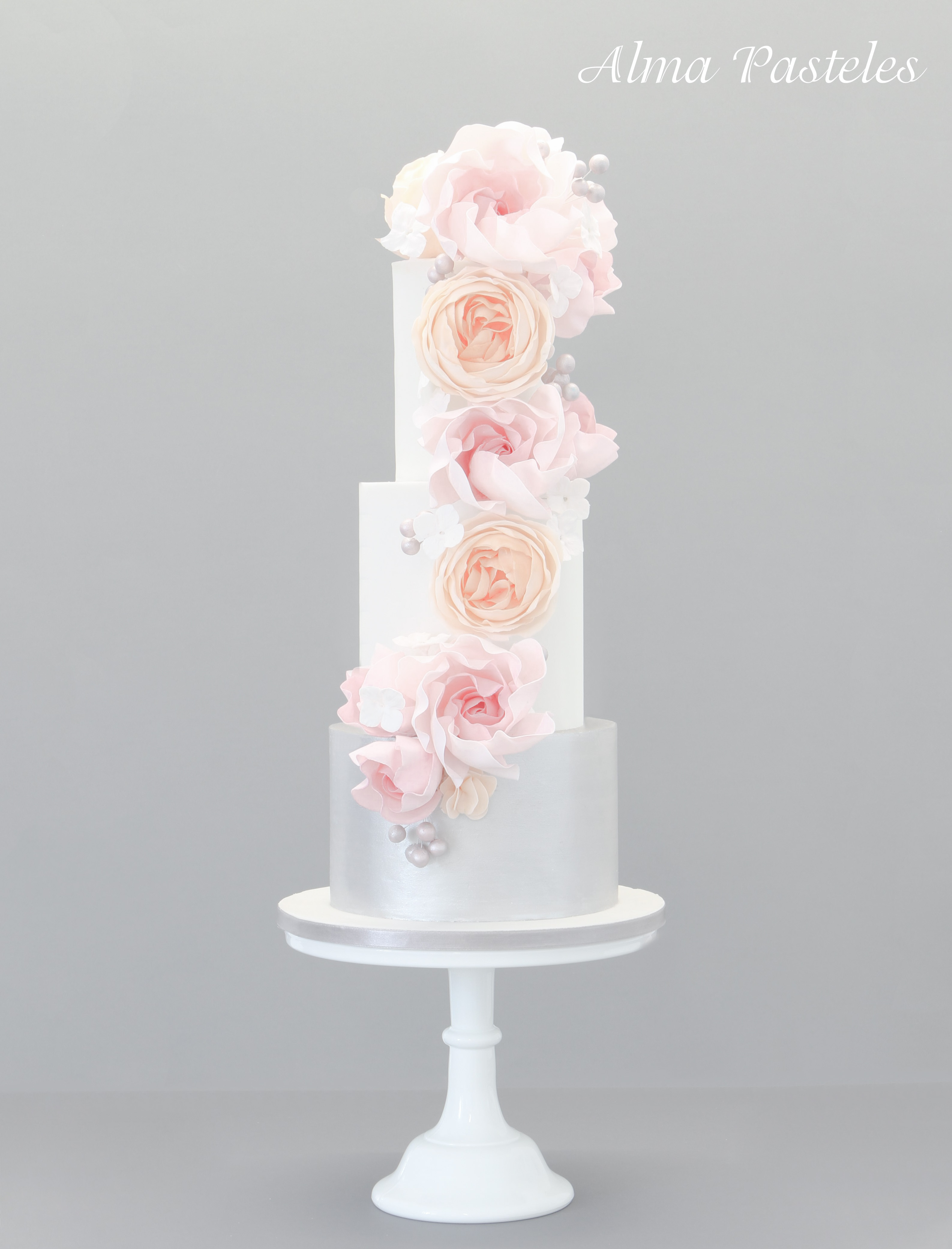 White and silver wedding cake with light pink cascading sugar flowers