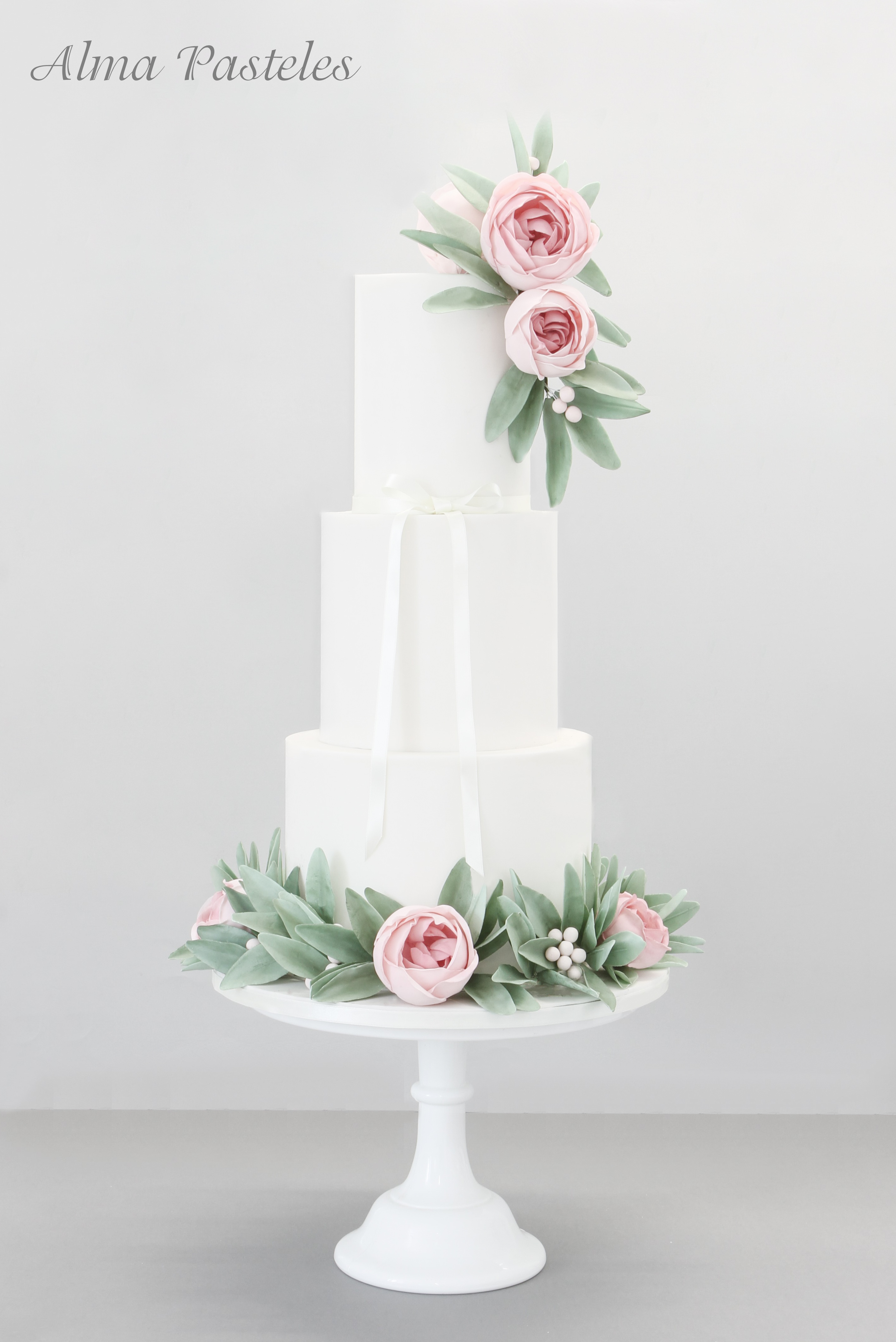 White wedding cake with sugar leaves and flowers