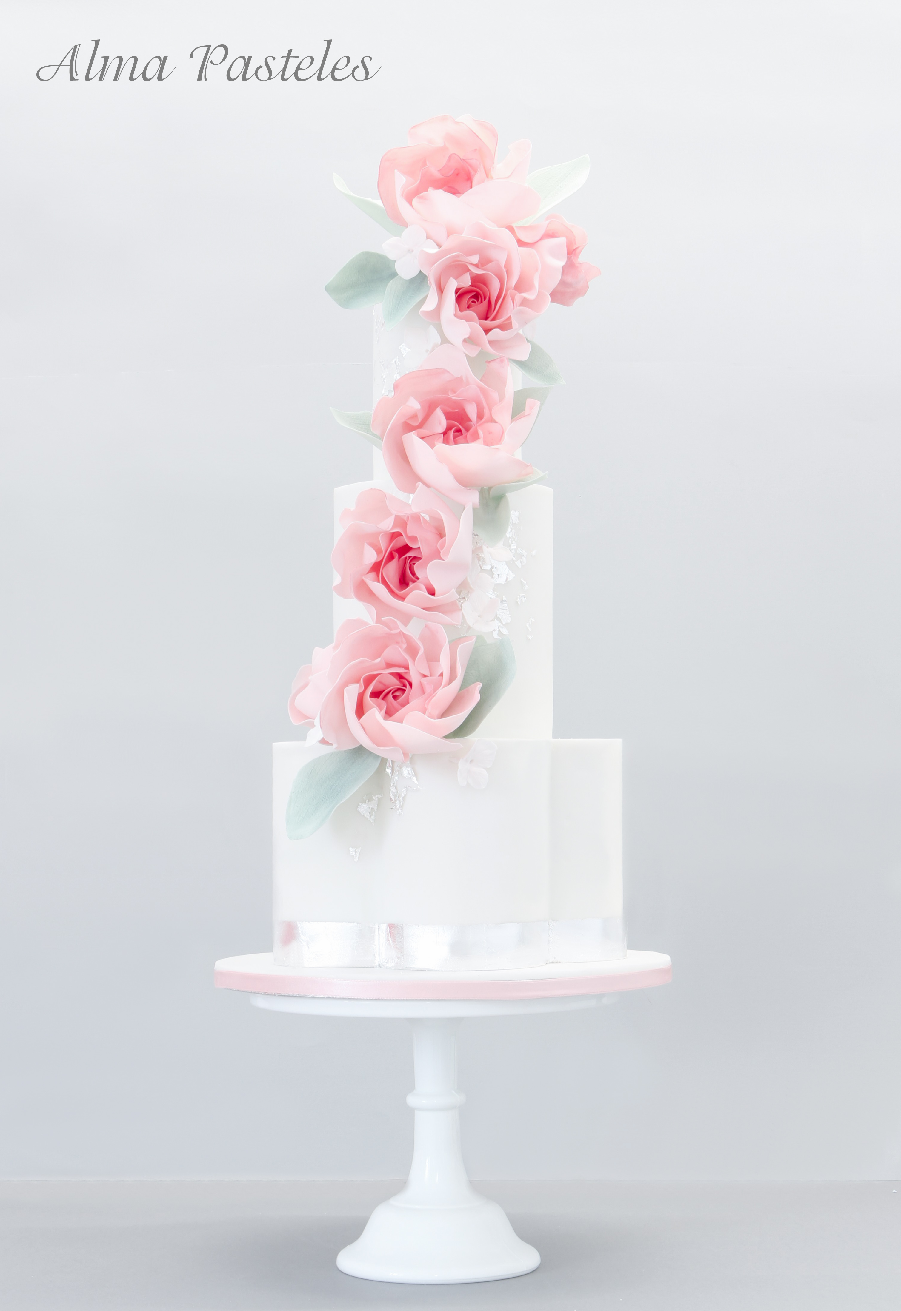 White wedding cake with cascading pink sugar roses