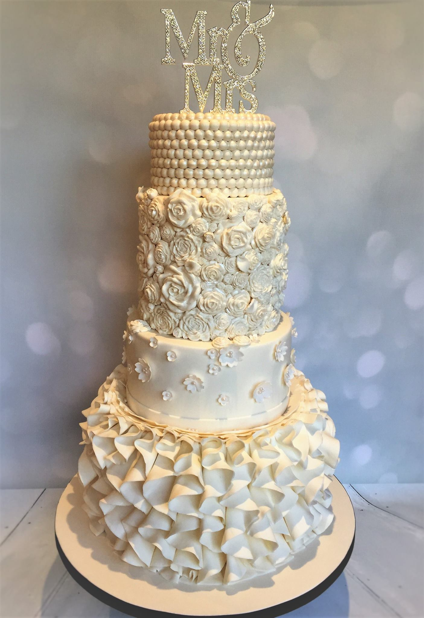 Ivory wedding cake with rosettes and ruffles