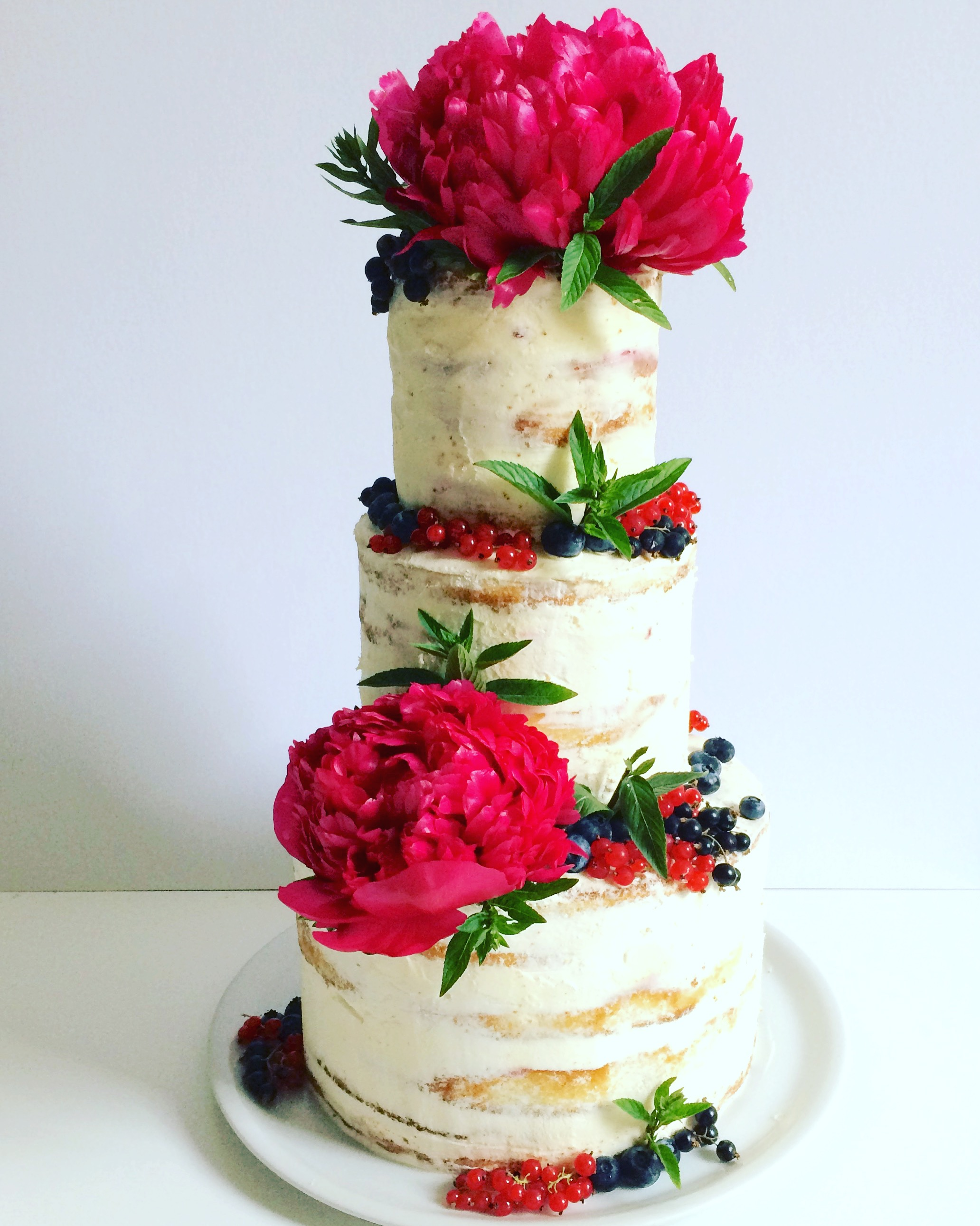 Naked wedding cake with large red sugar flowers