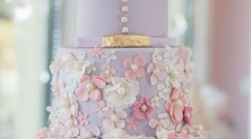 All lavender wedding cake covered in small pink sugar flowers