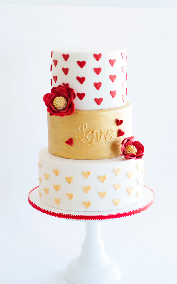 Red white and gold fondant valentine's day themed wedding heart cake with sugar flowers