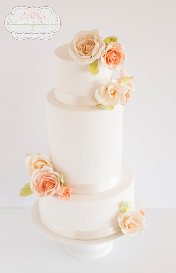White tiered fondant wedding cake with peach sugar flowers