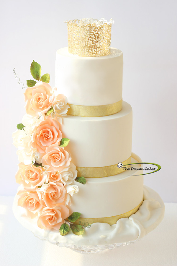 Ivory and peach wedding cake with gold sparkle
