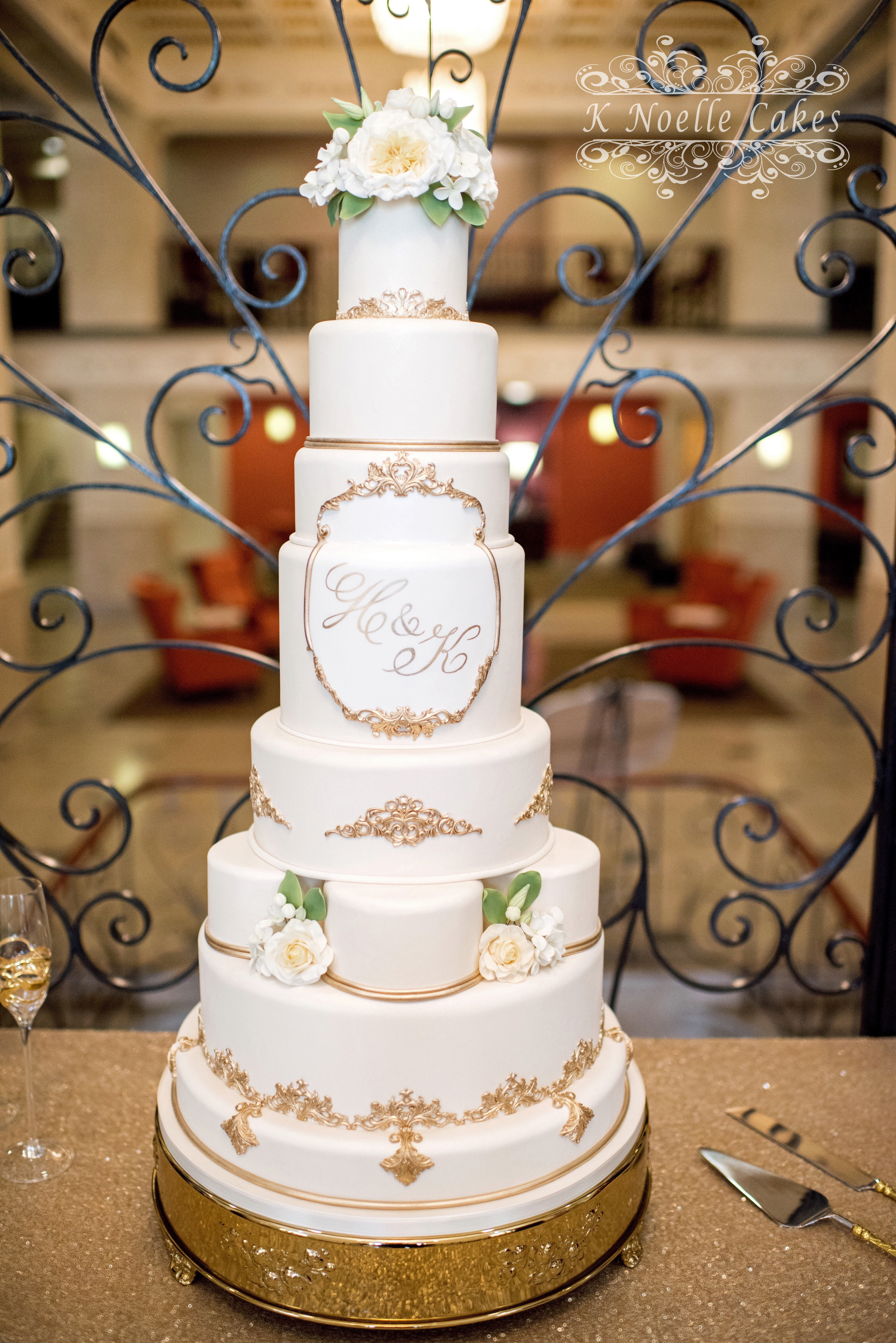 White wedding cake with gold detailing and sugar flowers