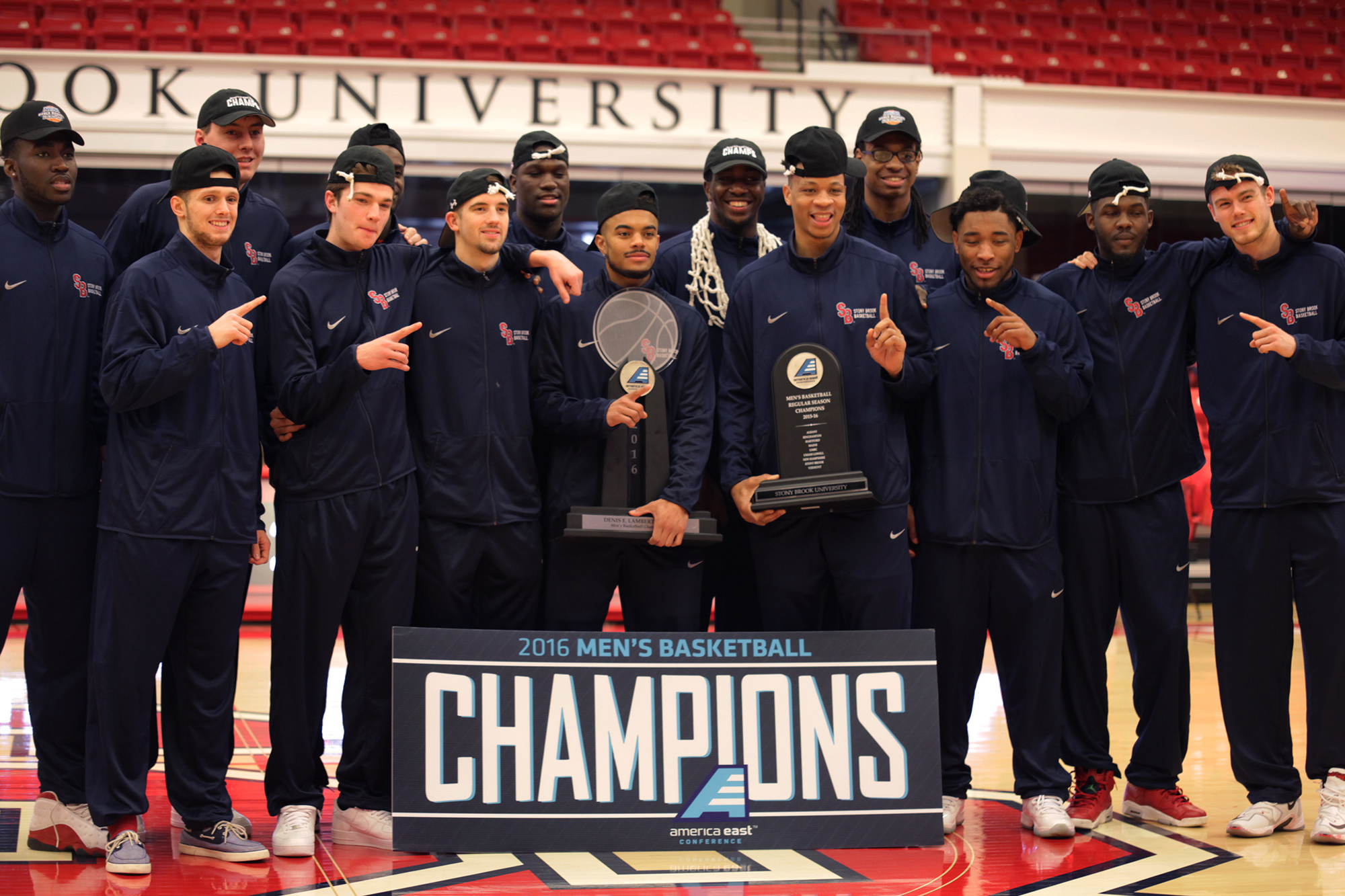 The Stony Brook Men's Basketball team poses with the team's championship trophy and banner at Sunday Selection for the NCAA tournament. ANDREW EICHENHOLZ/THE STATESMAN