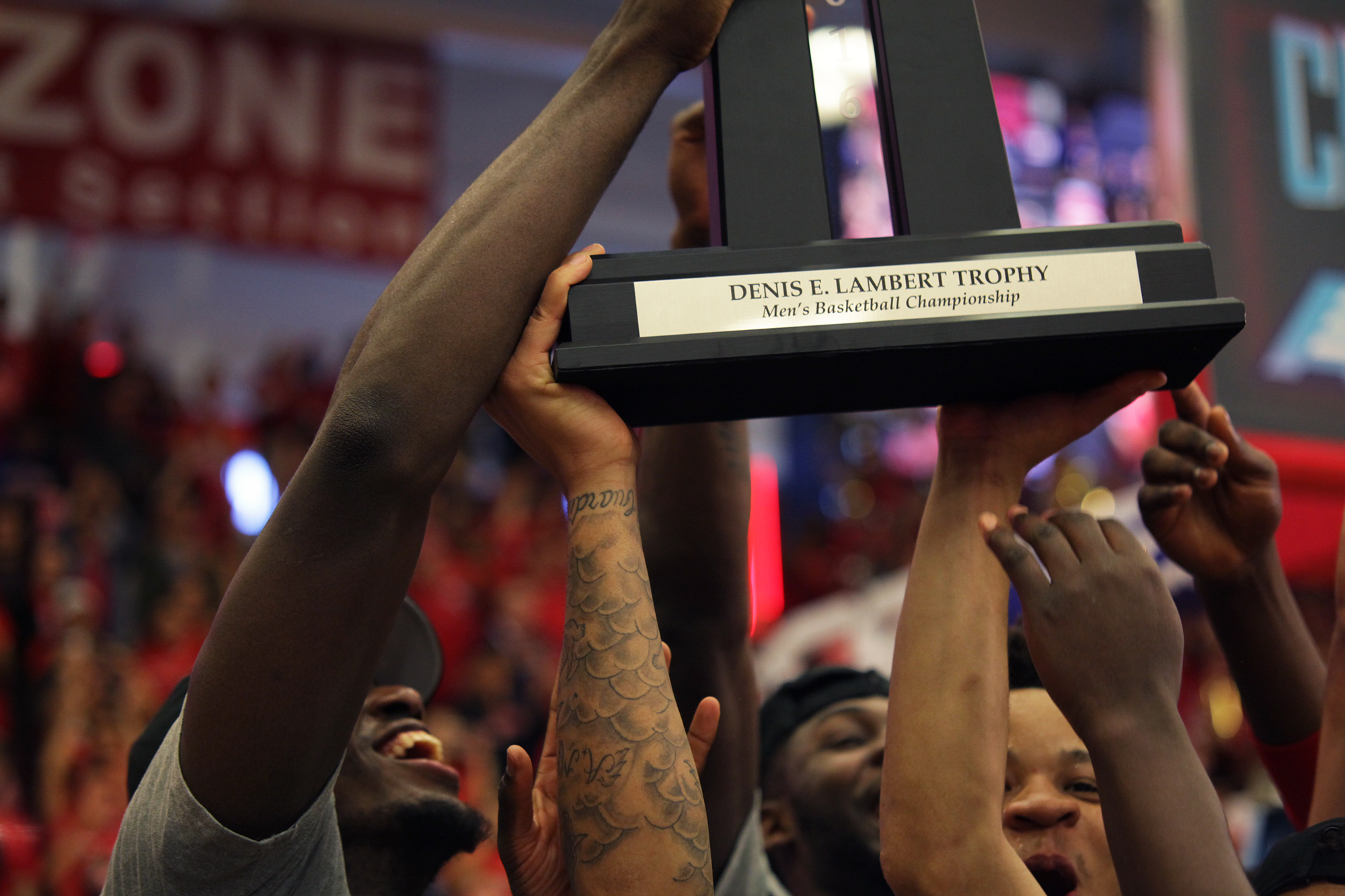 Members of the Stony Brook Men's Basketball team hold up their championship trophy after defeating Vermont.  CHRISTOPHER CAMERON/THE STATESMAN