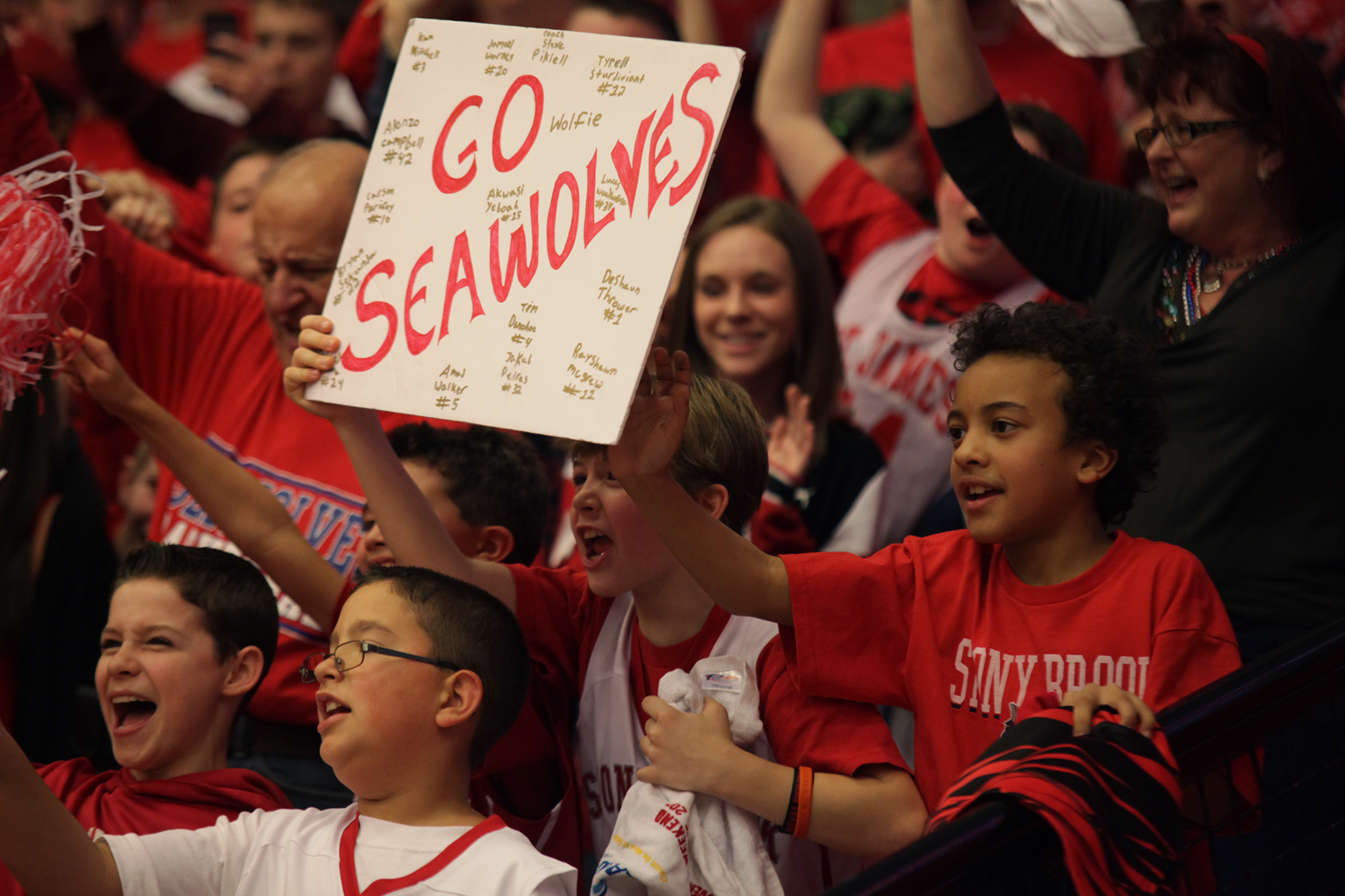Young Stony Brook fans hold up a poster signed by members of the Stony Brook Men's Basketball team during their championship game. CHRISTOPHER CAMERON/THE STATESMAN