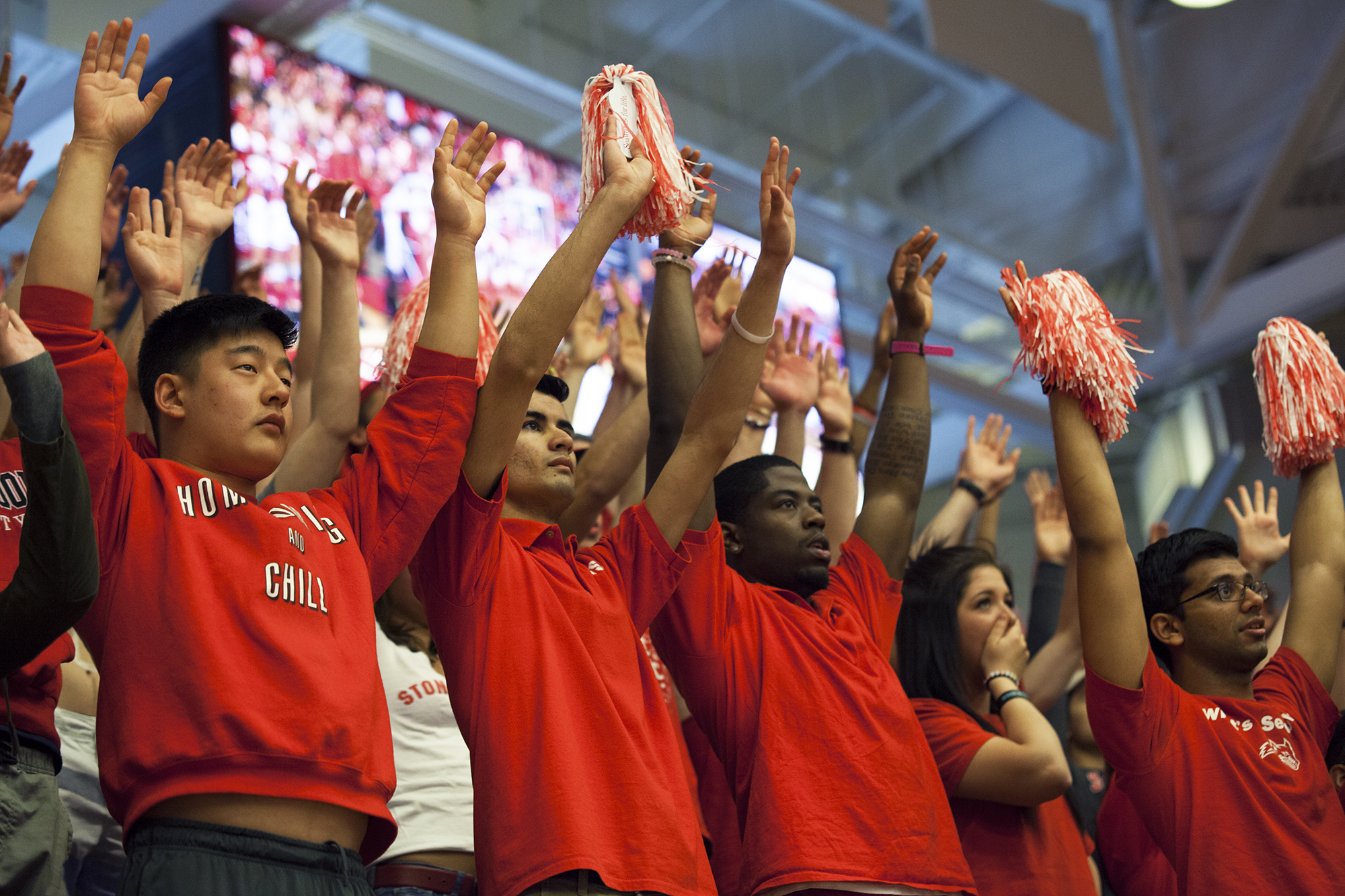 Stony Brook fans silently hold their arms up in support of senior guard Carson Puriefoy as he takes a free throw shot. CHRISTOPHER CAMERON/THE STATESMAN
