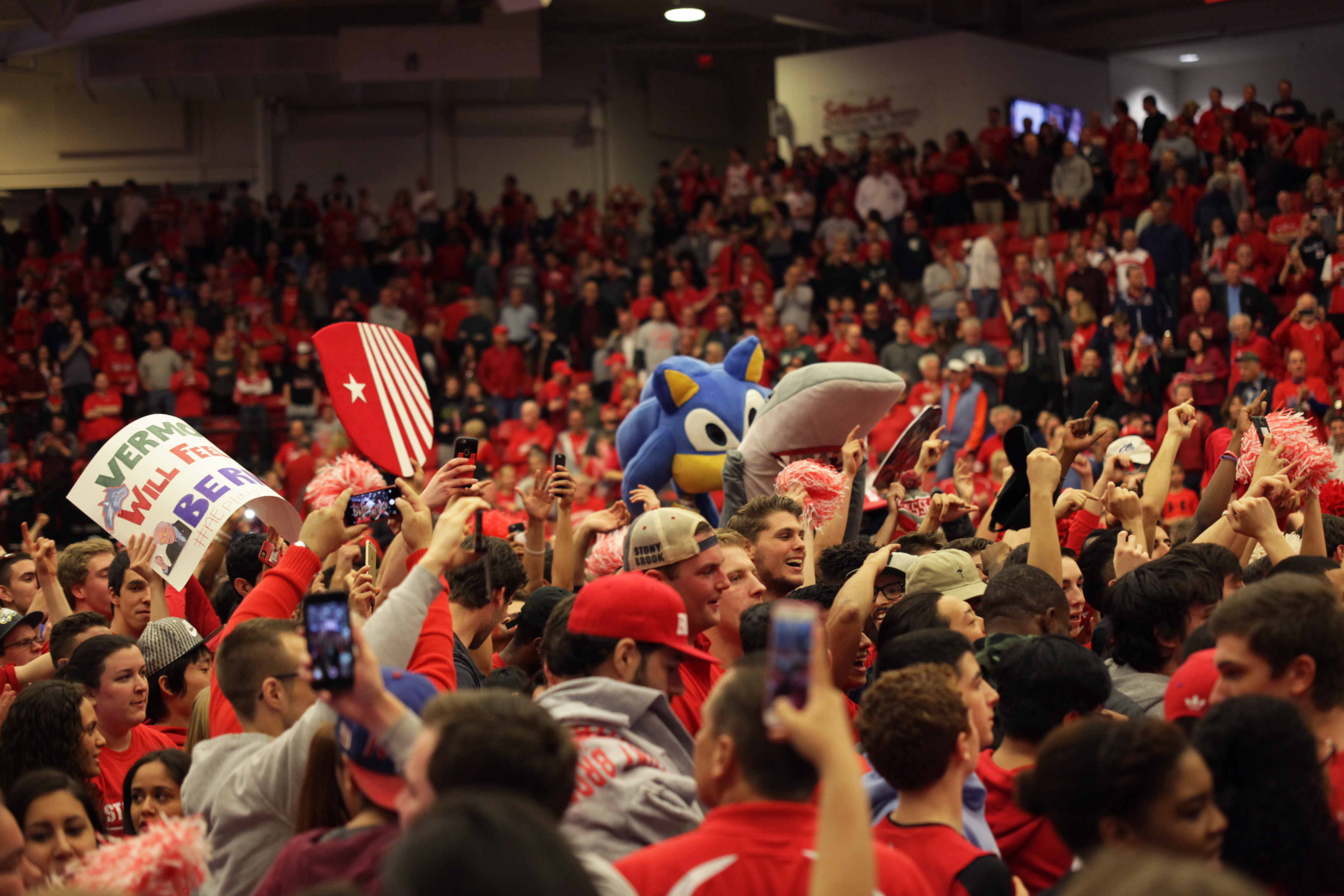Stony Brook fans storm the court to celebrate their comeback victory against Vermont in the America East Men's Basketball championship game. CHRISTOPHER CAMERON/THE STATESMAN