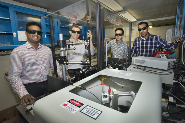 Matthew Eisaman, Ph.D., center, in a laser lab at Brookhaven Lab with co-authors, from left, Nanditha Dissanayake, Yutong Pang and Ahsan Ashraf. PHOTO CREDIT: STONY BROOK UNIVERSITY