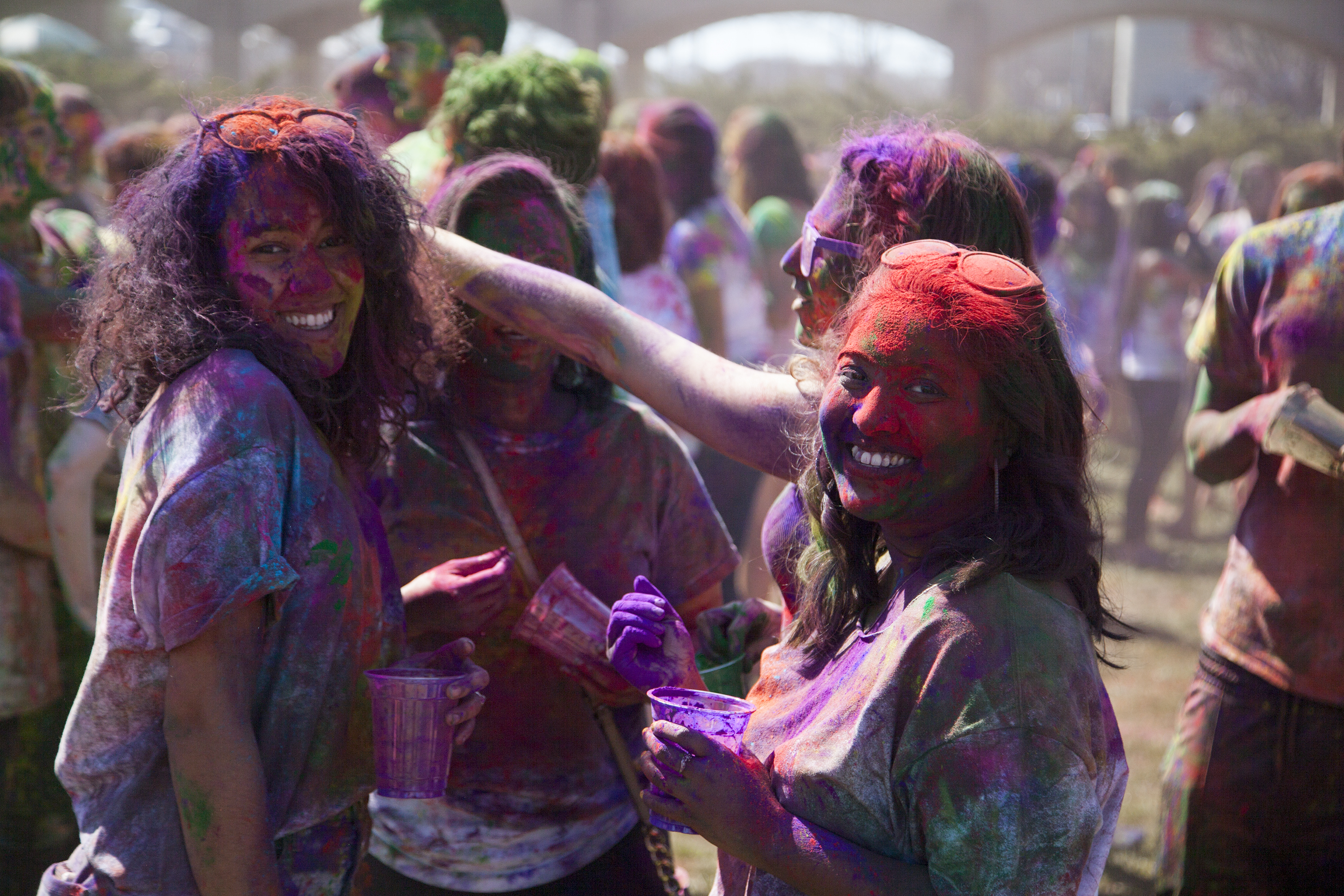 Catherine Rodriguez, left, Naurin and Stalla Saimon, right, celebrate Holi. ERIC SCHMID/THE STATESMAN