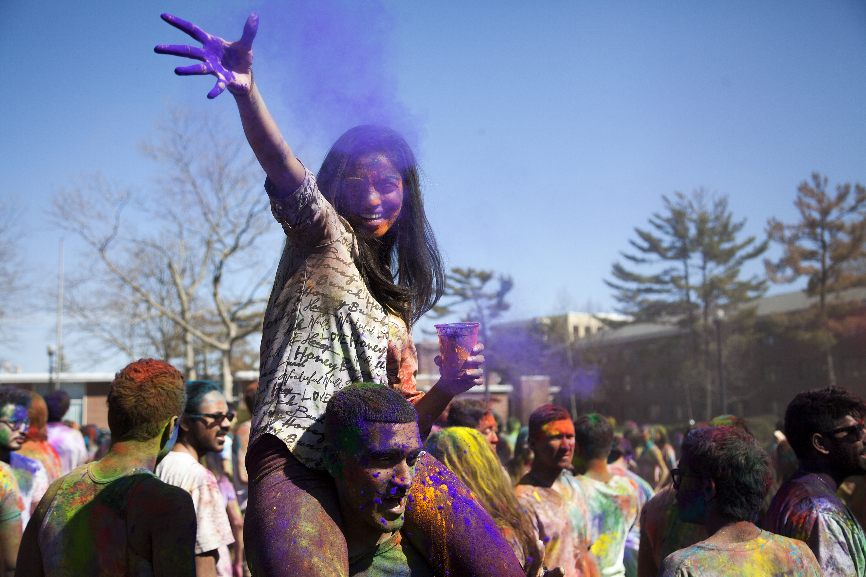 Aiswaria George, above, threw purple powder over the crowd while on Shadman Alam's shoulders at Holi on Sunday. ERIC SCHMID/THE STATESMAN