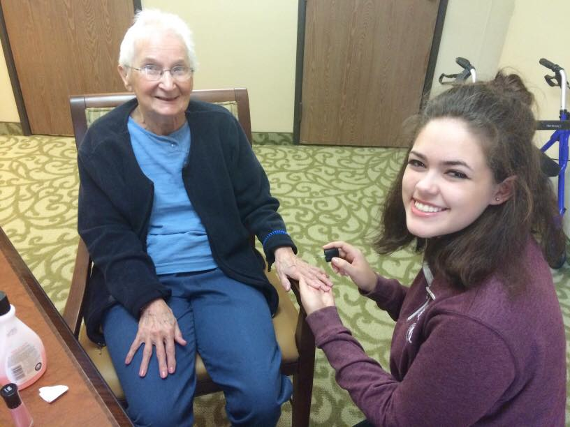 A member of the Hancock County GlamourGals chapter applies nail polish on Clarabelle,a senior citizen at Findlay Fox Run Assisted Living in Findlay, Ohio, in September. COURTESY OF HANCOCK COUNTY GLAMOURGALS