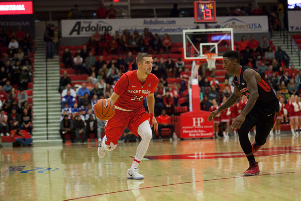 Senior guard Lucas Woodhouse (No. 34, above) drives the lane against Rutgers on Dec. 10. He leads the America East with 101 assists this season. ARACELY JIMENEZ/THE STATESMAN