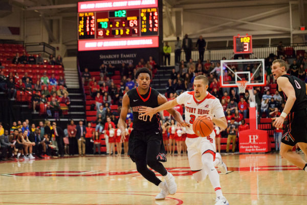 Senior guard Lucas Woodhouse drives to the basket against Northeastern Dec 3. He had a career-high 21 points against Albany, helping to propel Stony Brook to a 72-70 victory. ERIC SCHMID/THE STATESMAN