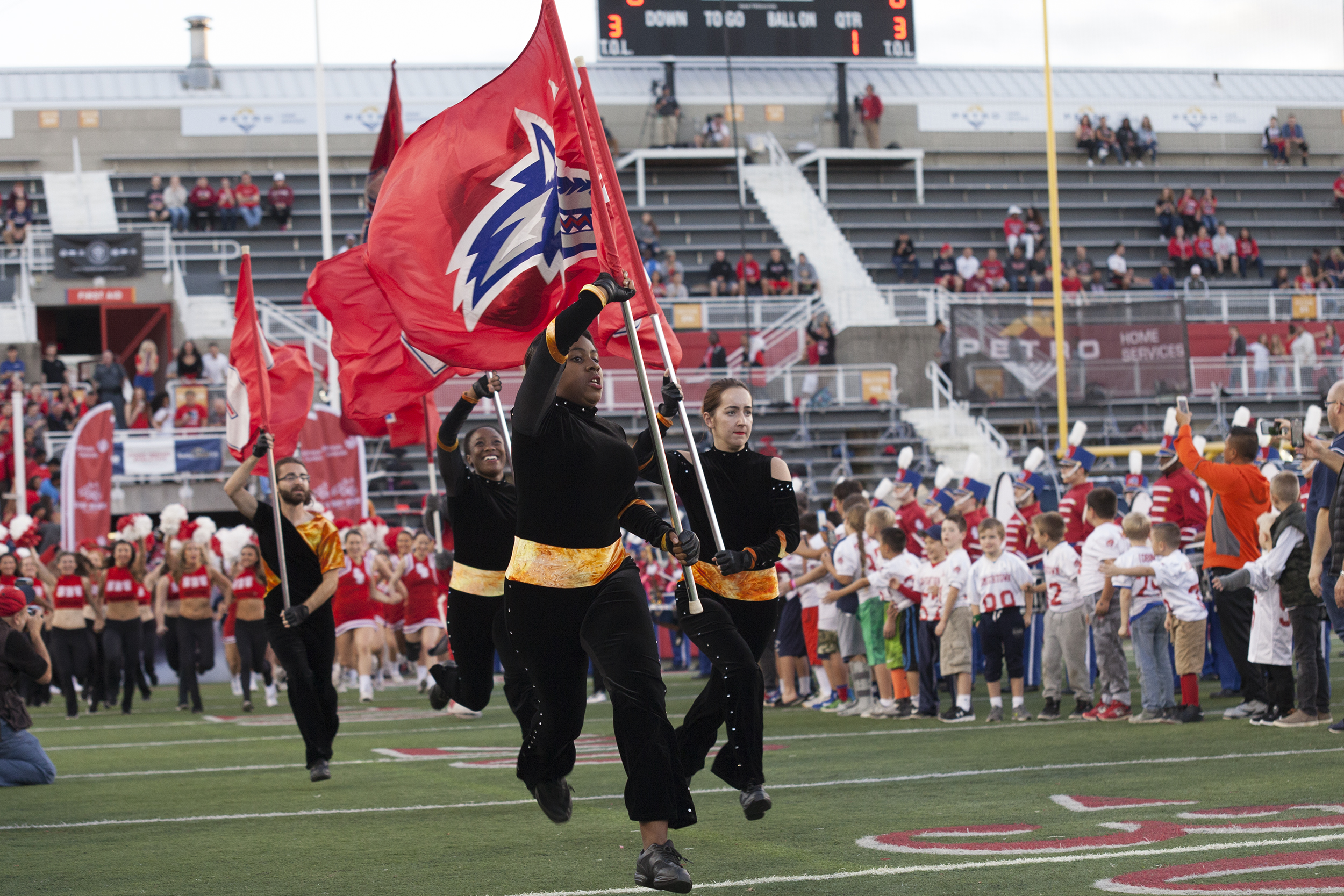 The color guard leads the charge with the Stony Brook cheerleading team, dance team and football team just before kickoff. <em>ARACELY JIMENEZ/THE STATESMAN</em>