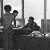 Michael Hucles (leaning) speaking with  Bernard Green (seated) while another person stands nearby
