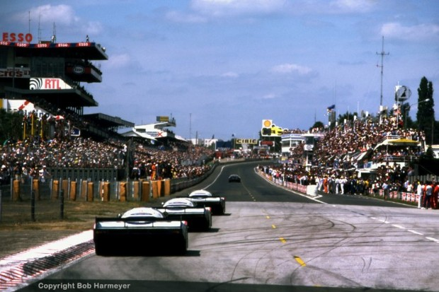 Running in formation, the Rothmans Porsche 956 team cars drive past the pit lane en route to a perfect 1-2-3 finish.
