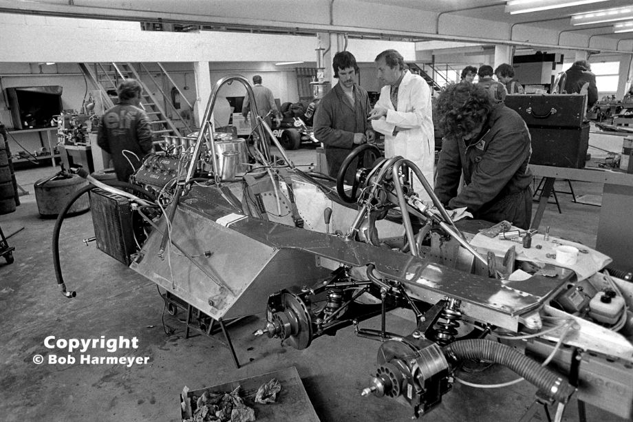 Derek Gardner (center, white coat), designer of the Tyrrell P34 six-wheel Formula 1 car, speaks with a crew member in the Tyrrell race shop near Ockham, Surrey. Gardner originally designed the car as a four-wheel drive entry for the Indianapolis 500, before USAC changed the regulations and abolished four-wheel drive machines.