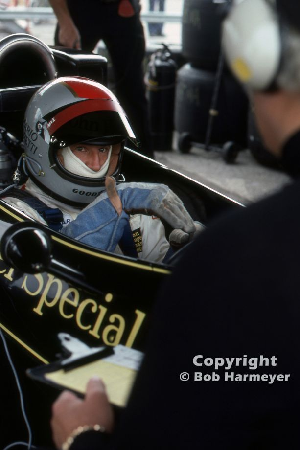 Mario Andretti, sitting in his Lotus 77, gestures with his hand as he speaks with designer Colin Chapman during practice for the 1976 Grand Prix of Sweden. Andretti qualified the Lotus on the pole.