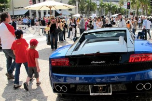 A new Lamborghini decorates the south end of Rodeo's three golden blocks, as more spectators join the day's estimated 40,000 on foot here for the show.