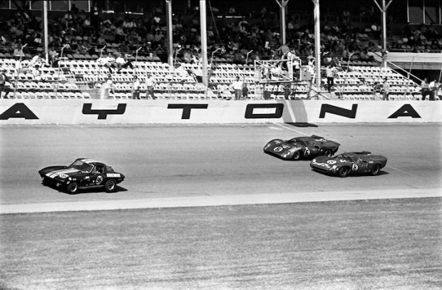 <strong>The eventual first and second place finishing Lola T70 Mk IIIs pass the start/finish line in front of the grandstands at the 1969 24 Hours of Daytona.  About to get lapped is the #96 Corvette of Smoky Drolet, John Tremblay and Vince Gimondo.  The Corvette finished 16th overall and first in the GT 5.0+ class, 94 laps behind the winner.</strong>
