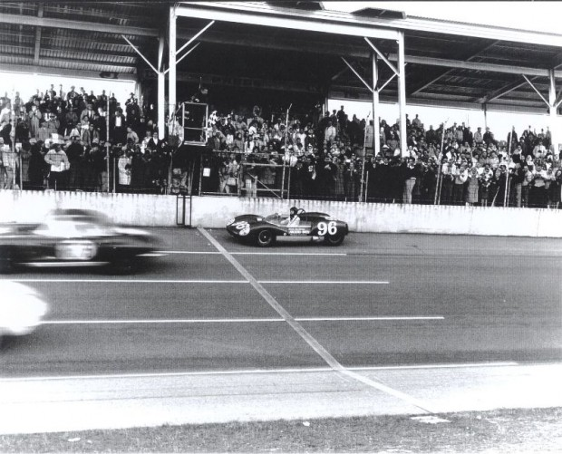 The checkered flag is waved and the Gurney Lotus moves toward the finish line.