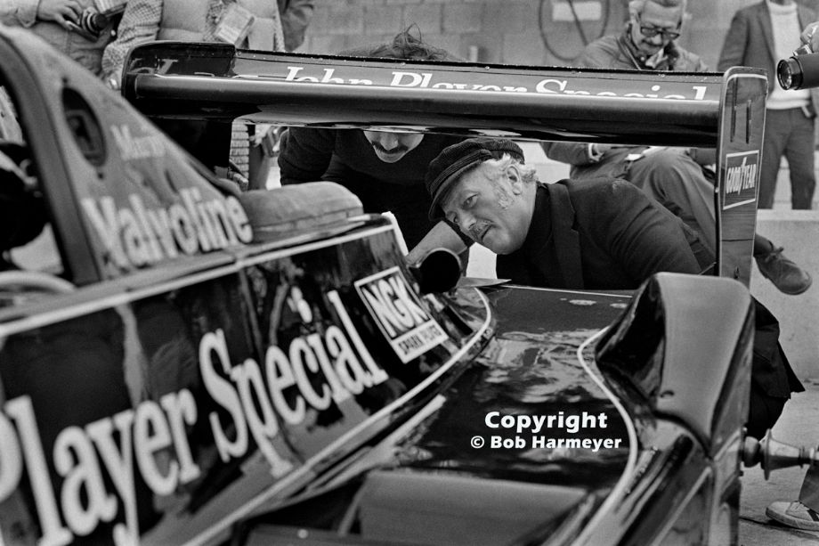 Colin Chapman inspects the back of Mario Andretti's Lotus 79 in the pit lane before practice for the 1978 United States Grand Prix East at Watkins Glen.