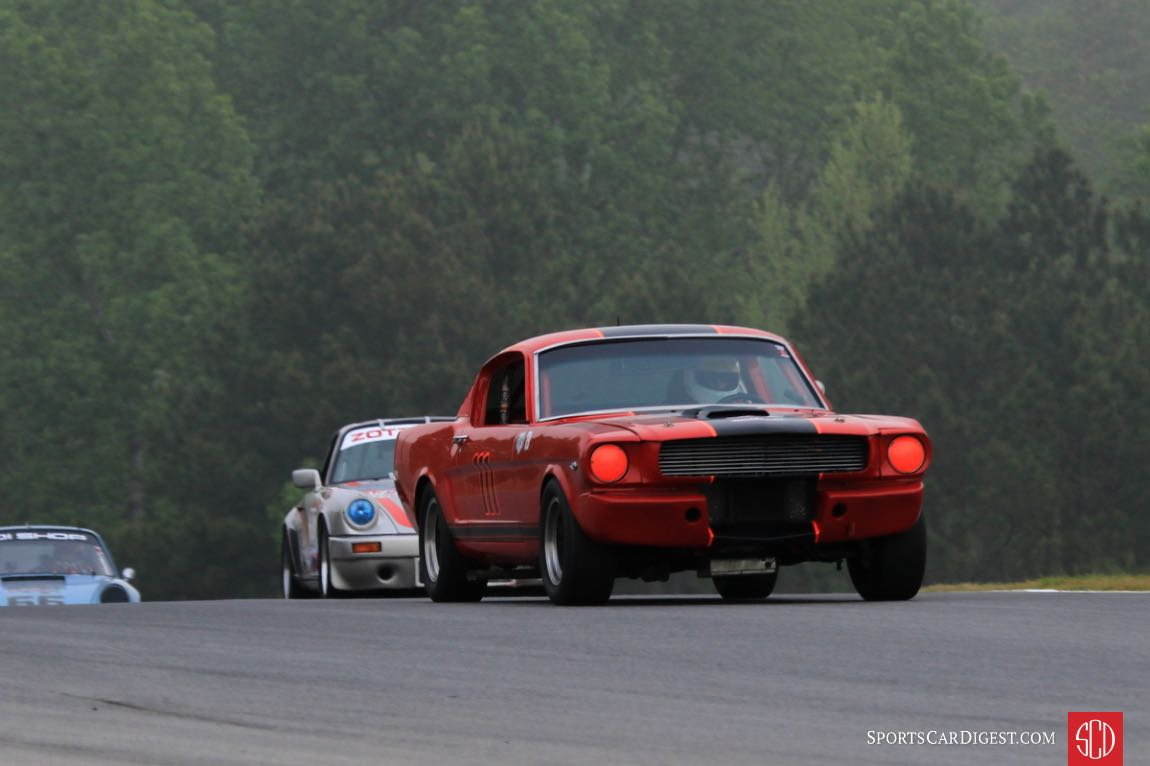 Dickson Rathbone, 66 Mustang 2+2 leads two Porsches through turn two.