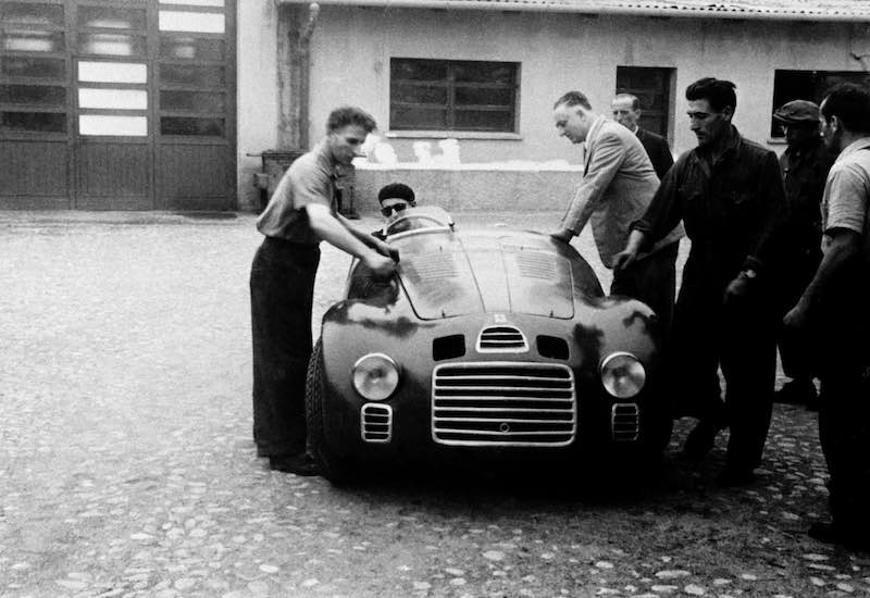 Enzo Ferrari with the 125 S in the courtyard of the Fabbrica - at the wheel was Ferdinando 'Nando' Righetti
