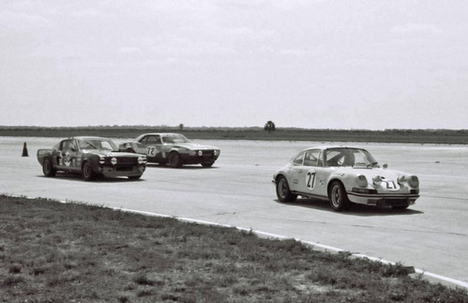 Mustang and a Camaro chase a Porsche 911S