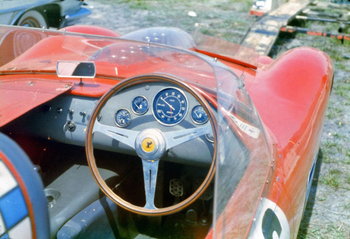 The cockpit of a Ferrari 250 TR at Sebring.  Note the small wind deflector just forward of the windshield.  This was to deflect bugs, oil and debris from the oversized windshields.  BARC boys photo.