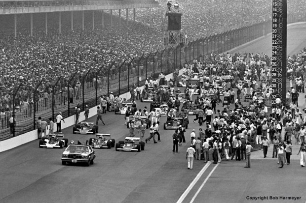 Following the Oldsmobile pace car driven by actor James Garner, the field begins to pull away from the starting grid for the 1977 event.